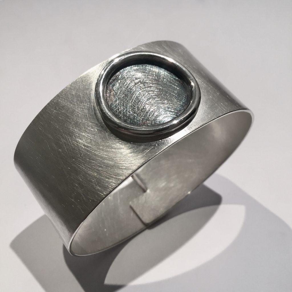 foto van een brede zilveren armband.